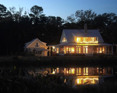 Lights reflected in pond behind house